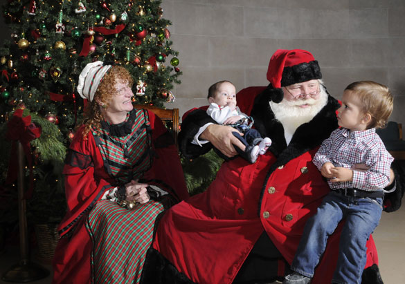 Children sit with Santa and Mrs. Claus at the Biltmore Christmas party