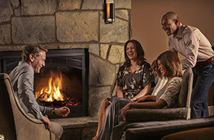 People gathered around a fireplace in Village Hotel